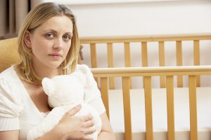bigstock-Sad-Mother-Sitting-In-Empty-Nu-13901726