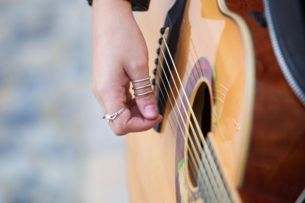 Κιθάρα και γυναικείο χέρι με πολλά δαχτυλίδια